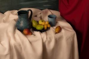 Blauer Krug mit Früchten auf Tisch