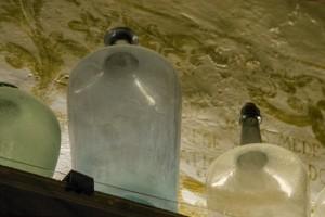 Stillleben mit großen Medizingefäßen vor alter Wand