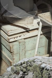 Hellgrüne Kiste mit bewachsenem Stein im Vordergrund